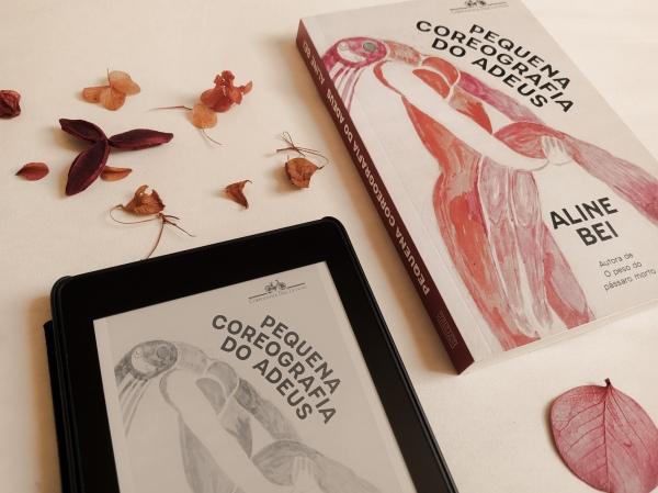 """Livro """"Pequena coreografia do adeus"""" ao lado de um kindle com a capa do mesmo título ao lado, dispostos em diagonal (canto inferior esquerdo ao canto superior direito), com folhas secas em torno dos objetos."""