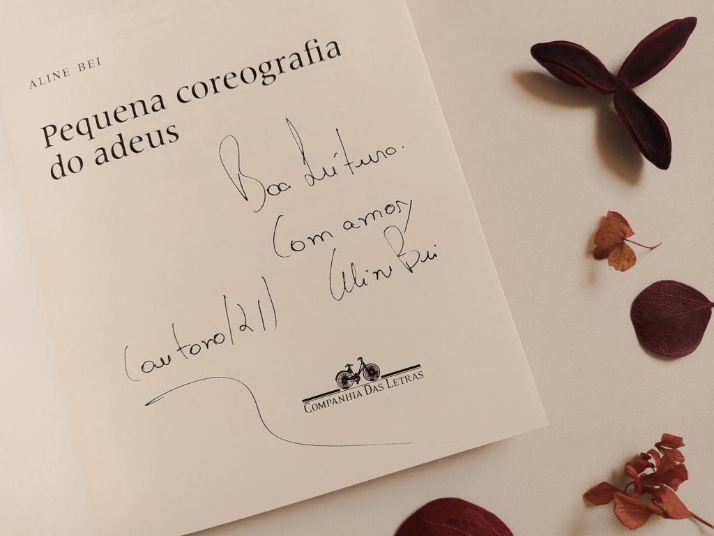 """Livro """"Pequena coreografia do adeus"""" aberta na folha de rosto, com o autógrafo da autora, onde se lê: """"Boa leitura. Com amor, Aline Bei (outono/21)"""". Há folhas secas ao redor do livro."""