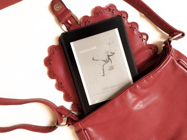 """Kindle com a capa do livro """"vida peregrina"""" saindo de uma bolsa de passeio aberta."""