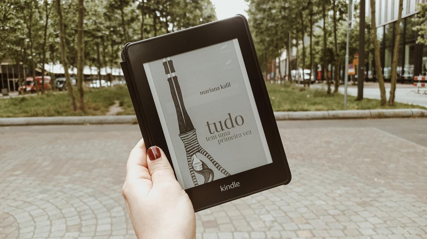 """Mão da Carol segurando um Kindle com a capa do livro """"Tudo tem uma primeira vez"""". Ao fundo, desfocado, estão árvores de um parque."""